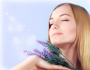 Young woman enjoying lavender flower scent, close up on clean skin female face, sensual girl at spa aromatherapy, health and beauty treatment, wellness concept